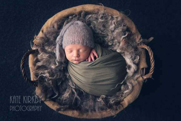 Swaddled newborn in basket on a fluffy rug